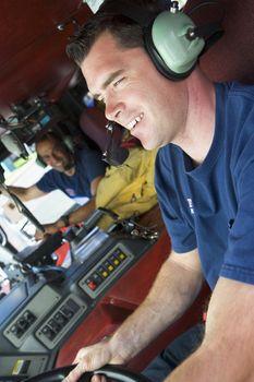 A firefighter driving a fire engine