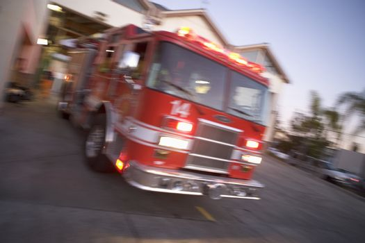 Fire engine rushing out of a fire station