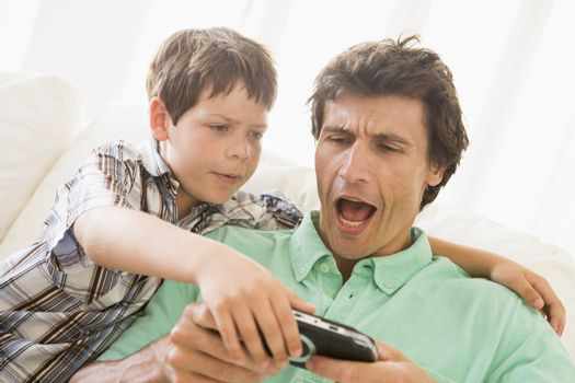 Young boy taking handheld game from unhappy man
