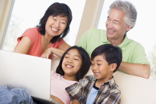 Couple with two young children in living room with laptop smiling