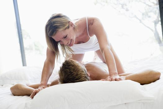 Couple lying in bed being playful and smiling