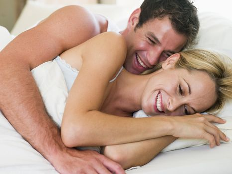 Couple lying in bed laughing