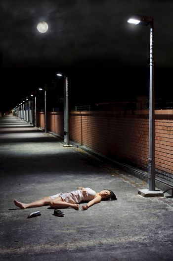 Woman lies vulnerable in the vacant street