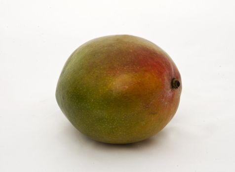 an almost ripe mango on white background