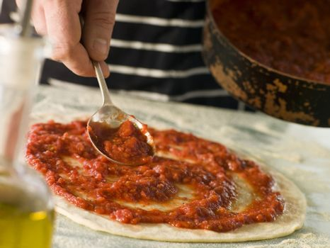 Spooning Tomato sauce onto a Pizza Base