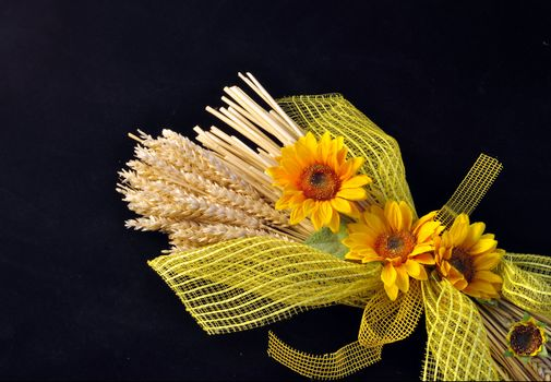 Decoration consists of stalks of wheat and sunflowers on a black background.