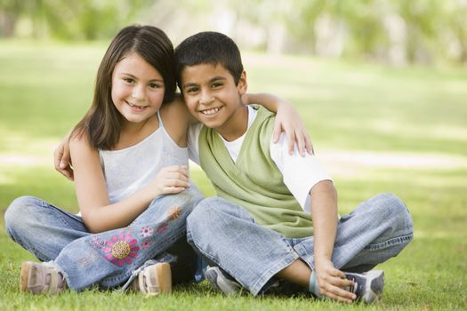 Two young children outdoors in park bonding and smiling