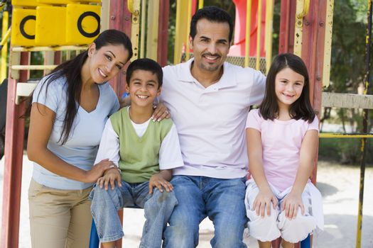 Family sitting on playground structure smiling