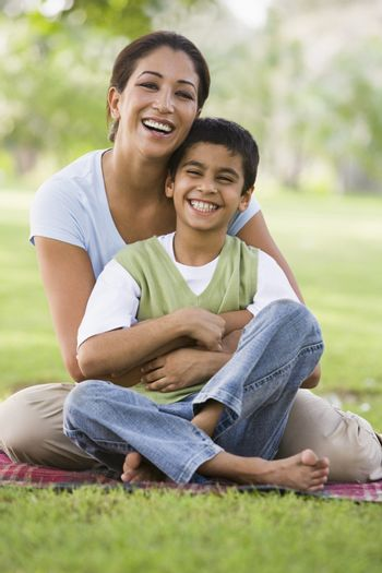 Mother and son outdoors in park bonding and smiling