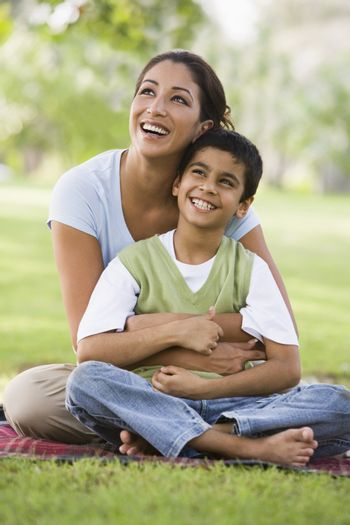 Mother and son outdoors in park bonding and smilingMother and son outdoors in park bonding and smiling