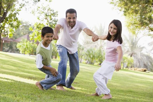 Family outdoors in park bonding and smiling