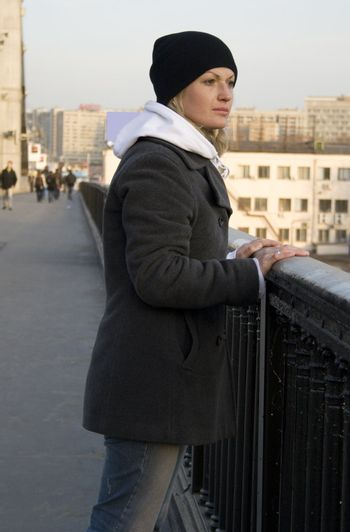 The thoughtful pretty womanl on the bridge