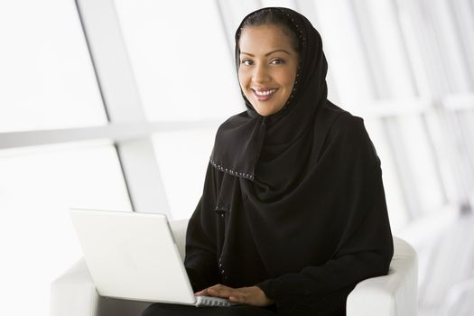 Woman sitting indoors smiling