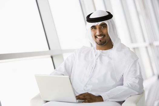 Man indoors with laptop smiling