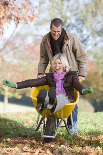 Man outdoors pushing woman in wheelbarrow and smiling