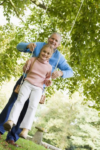Grandfather pushing granddaughter on swing and smiling