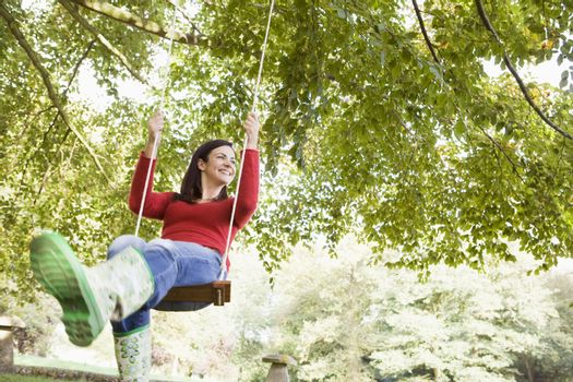Woman outdoors swinging on tree swing and smiling