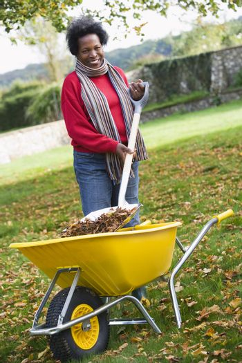 Woman outdoors shoveling leaves into wheelbarrow and smiling