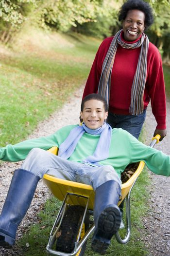 Mother outdoors pushing son in wheelbarrow and smiling