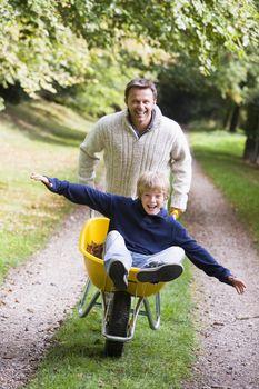 Father and son walking on path pushing wheelbarrow