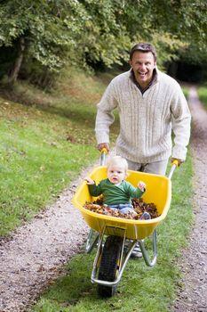 Father pushing baby son in wheelbarrow