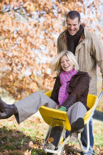 Family playing outdoors with wheelbarrow and smiling