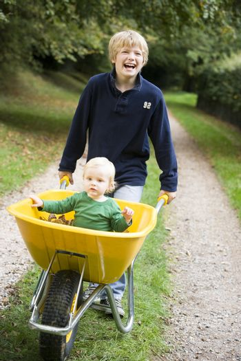 Young boy pushing baby brother in wheelbarrow