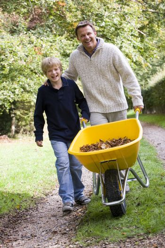 Father and son pushing wheelbarrow on path