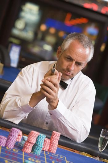 Man in casino playing roulette and smoking cigar