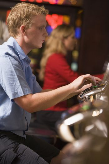 Man in casino playing slot machine with people in background