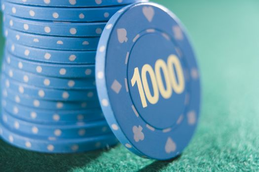 Poker chips piled on a poker table with one thousand chip showing