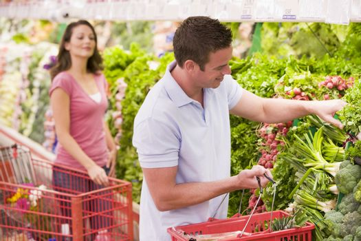 Couple flirting in supermarket aisle