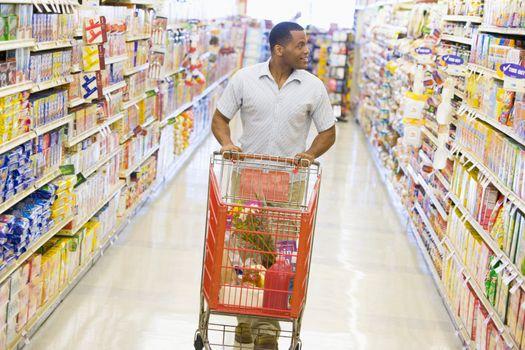 Man pushing trolley along supermarket aisle
