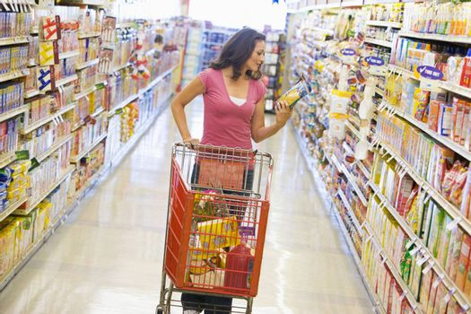 Woman shopping in supermarket aisle