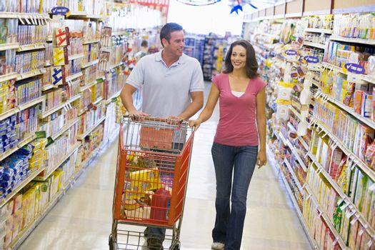 Couple shopping in supermarket aisle