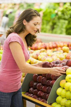 Woman choosing apples in produce department