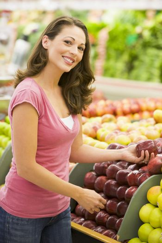Woman choosing apples at produce counter