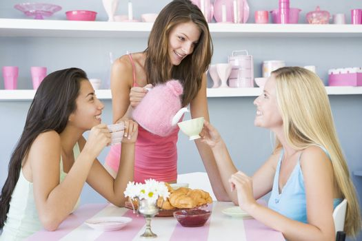 Three young women having a cold drink in a cafeteria