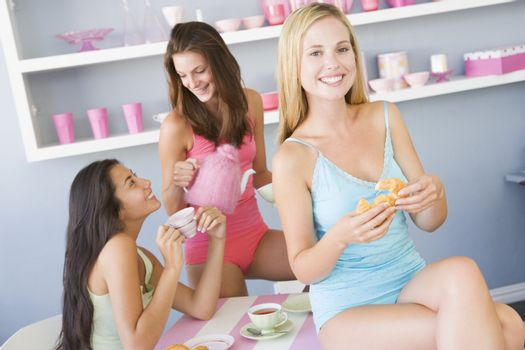 Three young woman sitting at a table having tea and a snack