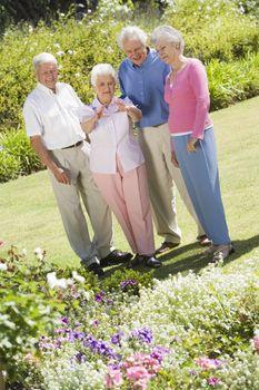 Group of senior friends in garden admiring flowerbed