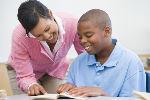 Elementary school teacher helping pupil