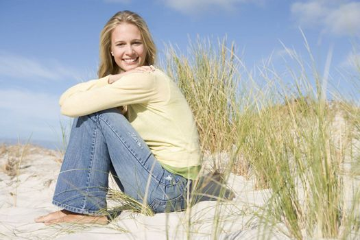 Young woman sitting amongst dunes