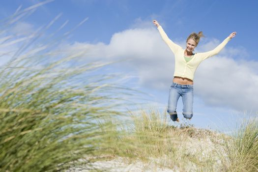 Young woman jumping amongst dunes