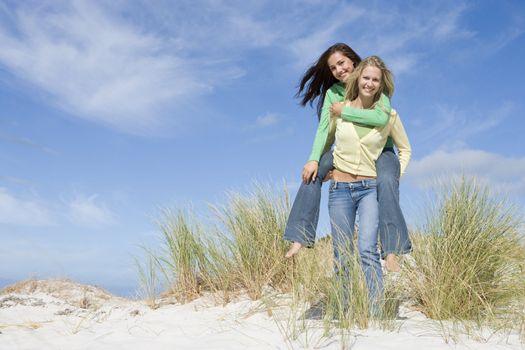 Two young women having fun in dunes