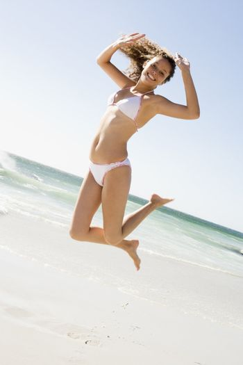 Woman leaping on beach