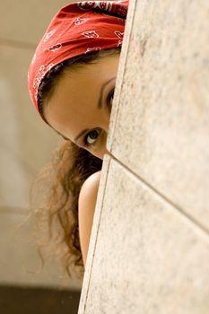 woman looking behind a wal