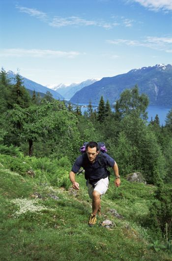 Man outdoors hiking up hill