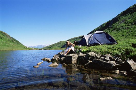 Woman at campsite sitting near river