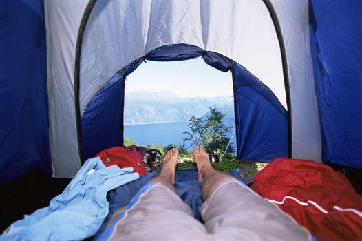 Man's legs in tent overlooking scenic location