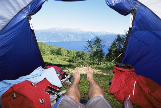 Man's legs in a tent overlooking scenic location